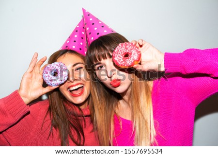 Portrait of two hungry young asian women holding two donuts isolated over  grey background.Picture of amazing two women friends eating donuts isolated over pink background. Looking camera