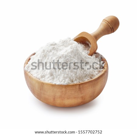 Wooden Bowl with flour and flour spoon. Rice or wheat flour isolated on white background. #1557702752