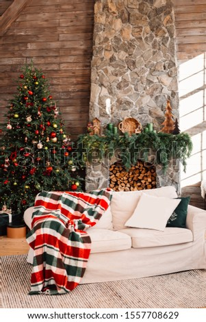 Christmas interior. Christmas tree and large fireplace in a bright wooden room. Chalet. House in the Alps. #1557708629