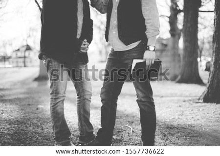 A grayscale shot of two males talking to each other while holding the bible with a blurred background #1557736622