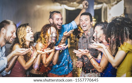 Multiracial happy friend having fun at new year's eve celebration - Young people blowing confetti at after party in night club - Friendship concept on cool entertainment mood - Focus on blue shirt guy #1557770645
