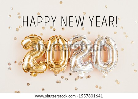 New year 2020 celebration. Gold and silver foil balloons numeral 2020 and confetti on pink background. Flat lay #1557801641