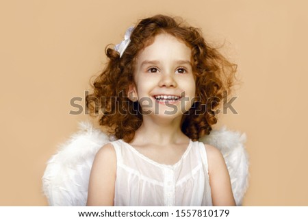 Little girl smiling, looking at a side, with wings in white dress, over beige background. Valentines day cupid. #1557810179