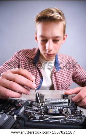 Man repairing broken computer, video card,memory RAM, cooler, processor,hard drive. Young repairer working with screwdriver in service center.teenager  #1557821189