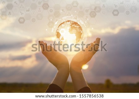 Concept global business and technology. Hand showing business icons and globe at sunset. #1557856538