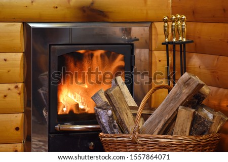A cozy corner with a stove and firewood. Fire in fireplace in wooden house. Firewood burns in stove. Warm atmospheric picture with fireplace in house. Stove in interior of a wooden home.