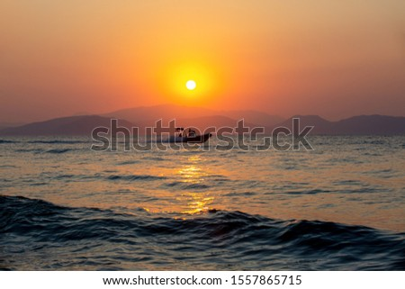 silhouette of fishing boat on front of sunset #1557865715