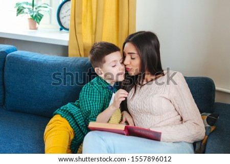Young woman and her little child reading book at home #1557896012