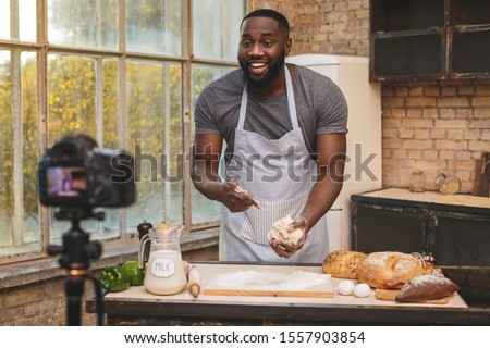 Baking process. Young cooking african man speaker talking on digital camera recording vlog. African male vlogger or shooting blog filming reportage advertising video, coaching.  Royalty-Free Stock Photo #1557903854