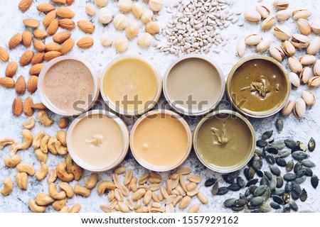 Nuts and seeds butter in jars with ingredients. Homemade raw organic peanut, almond, hazlenut, cashew, pistachio, macadamia nuts paste and sunflower and pumpkin seeds butter on a table. Top view. #1557929162