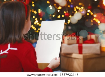 Back view of little girl holding blank white empty paper over Christmas festive background, mockup, free space #1557933146