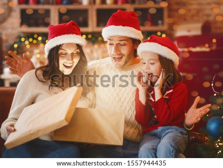 Christmas miracle. Surprised family of three looking into shining gift box, opening xmas presents together, kitchen interior