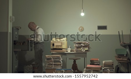 Corporate businessman searching for files in a rundown messy office with outdated computer and piles of paperwork #1557952742