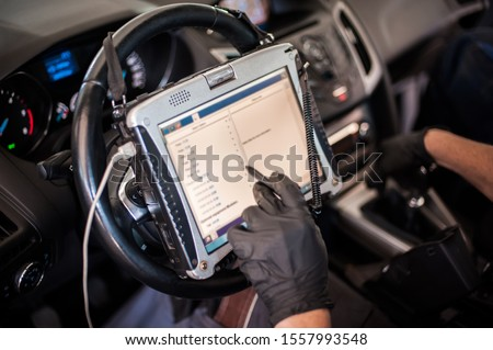 Automobile computer diagnosis. Car mechanic repairer looks for engine failure on diagnostics equipment in vehicle service workshop Royalty-Free Stock Photo #1557993548