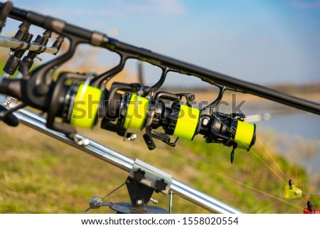 Close up view of multiple carp fishing reel coil on rods on rod pod near lake river. Fishing during sunset #1558020554