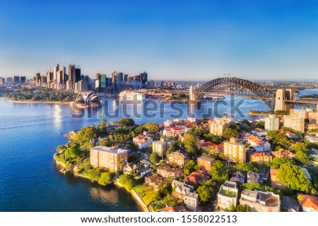 Waters of Sydney harbour between city CBD landmark builidings connected by the Sydney Harbour bridge to North Shore wealthy suburbs - elevated aerial view on a sunny day. Royalty-Free Stock Photo #1558022513