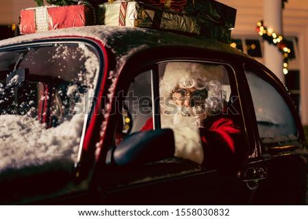 Portrait of Santa Claus. Santa Claus is driving his red car #1558030832