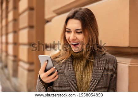 Happy girl with mobile phone in cold weather in street. Young woman using smart phone in winter #1558054850