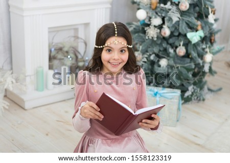 Must read for Christmas season. Happy small child read book by xmas tree. Adorable little girl read Christmas story. Turn pages of your imagination, read. #1558123319