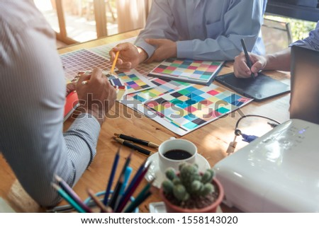 Group of Asian designers brainstorming working together with colleagues and color swatches in co-working workplace. #1558143020