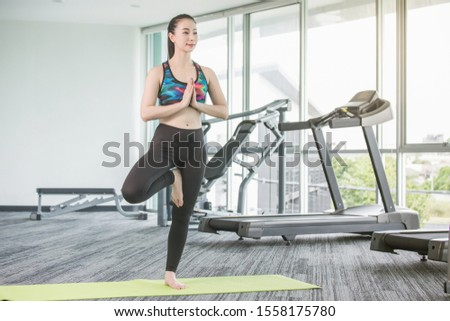 Full-length portrait of beautiful Asian woman doing yoga exercise tree-pose on yoga mat at fitness isolated on machine background with copy space healthy and lifestyle concept. #1558175780