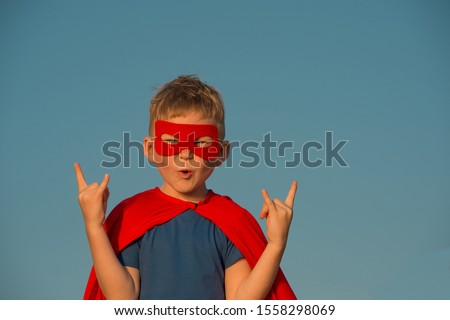 Little child superhero with red cloak and glasses. Happy smiling kid ready for adventure. Success, motivation concept. Little businessman isolated on blue, Boy superhero. Cool school boy. #1558298069