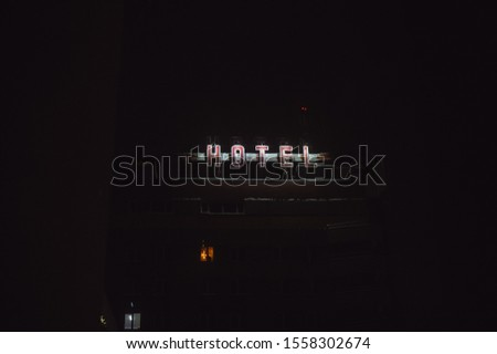 The word hotel glows in the night. Place for text #1558302674