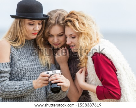 Female photographer showing fashion models results of photo shoot. Behind the scenes of professional modeling and photography industry. #1558387619