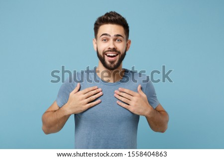 Young excited surprised handsome man in casual clothes posing isolated on blue wall background, studio portrait. People sincere emotions lifestyle concept. Mock up copy space. Keeping hands on chest #1558404863