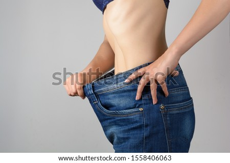 Torso of a young slim woman in big jeans. Results after training and diet. #1558406063