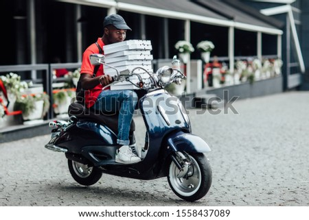 Young man courier poses on fast motorbike, carries rucksack, wears helmet, holding cardboard, looks aside with pleased expression. People, technology, transport. #1558437089