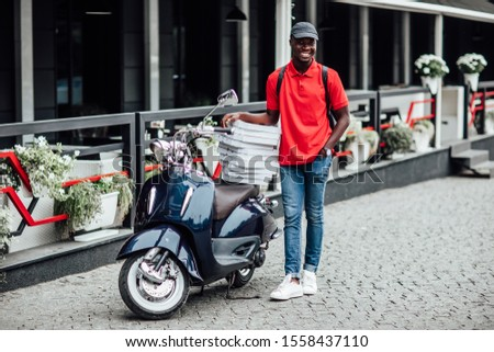 Busy african man, carries cardboard boxes with pizza, delivers to customers, poses on blue scooter, wears helmet, white t shirt and sportshoes, spreads legs, has happy expression. #1558437110