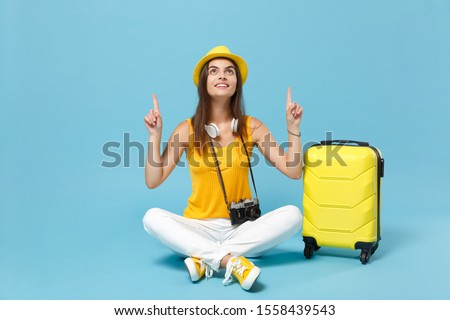 Traveler tourist woman in yellow casual clothes hat with suitcase photo camera isolated on blue background. Female passenger traveling abroad to travel on weekends getaway. Air flight journey concept #1558439543