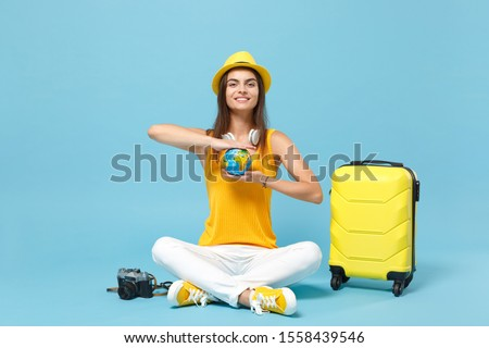Traveler tourist woman in yellow casual clothes hat with suitcase photo camera isolated on blue background. Female passenger traveling abroad to travel on weekends getaway. Air flight journey concept #1558439546
