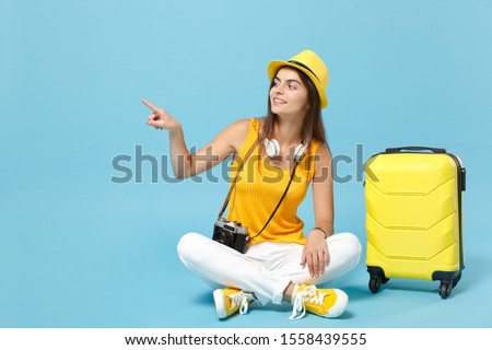 Traveler tourist woman in yellow casual clothes hat with suitcase photo camera isolated on blue background. Female passenger traveling abroad to travel on weekends getaway. Air flight journey concept #1558439555
