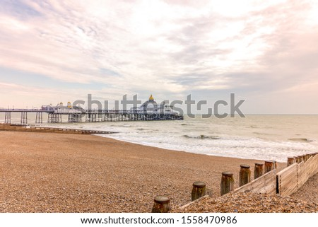 Early morning at a shingle beach in Eastbourne.  A wooden breakwater is in the foreground and a pier beyond. A dawn sky is above. #1558470986