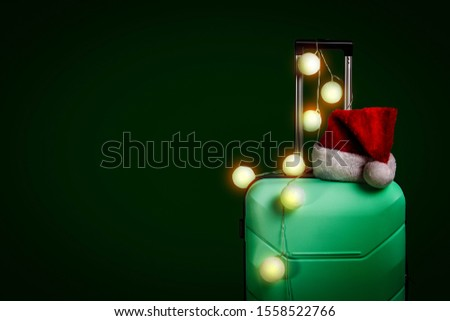 Plastic suitcase, Santa Claus cap and garland on a dark green background. Concept of travel, business trips, trips to visit friends and relatives on Christmas holidays. New Years journey #1558522766