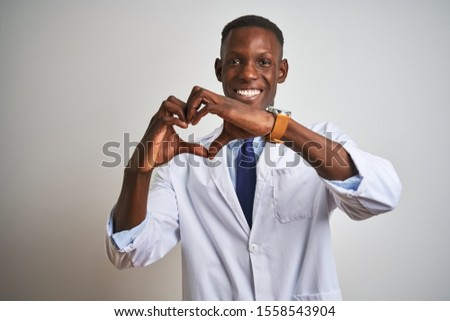 Young african american doctor man wearing coat standing over isolated white background smiling in love doing heart symbol shape with hands. Romantic concept. #1558543904