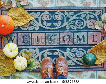 "Door mat decorated with yellow leaves and pumpkins, someone has come over and standing on the door mat with the caption ""welcome"", feet photo"