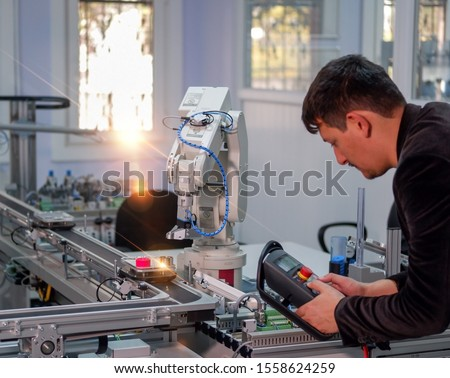 industry 4.0 concept: Man (engineer) is programming robotic arm with control panel (teach pendant) on smart factory production line background. Selective Focus. #1558624259