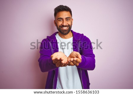 Young indian man wearing purple sweatshirt standing over isolated pink background Smiling with hands palms together receiving or giving gesture. Hold and protection #1558636103
