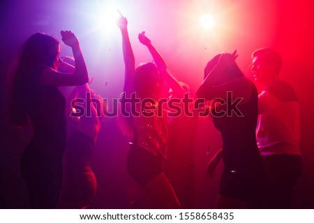 No troubles. A crowd of people in silhouette raises their hands on dancefloor on neon light background. Night life, club, music, dance, motion, youth. Purple-pink colors and moving girls and boys. #1558658435