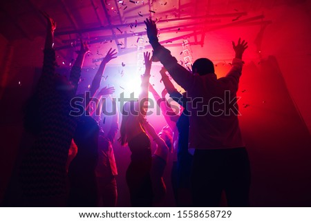 Active. A crowd of people in silhouette raises their hands on dancefloor on neon light background. Night life, club, music, dance, motion, youth. Purple-pink colors and moving girls and boys. #1558658729