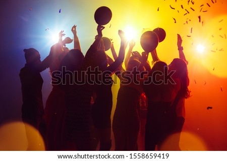 Balloons. A crowd of people in silhouette raises their hands on dancefloor on neon light background. Night life, club, music, dance, motion, youth. Yellow-blue colors and moving girls and boys. #1558659419