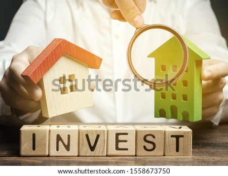 Wooden blocks with the word Invest and houses in the hands of a businessman. The concept of investing in real estate construction. Effective investment. Buying apartments. Business and finance #1558673750
