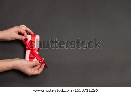Happy Holidays concept with woman hands holding present box with red bow on pastel dark background. Holiday card or holiday shopping on boxing day or black friday. #1558711226