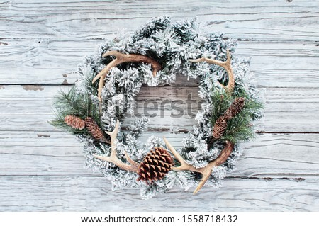 Flocked country or hunters Christmas wreath over white wooden background.  Made with pine cones, fir branches, and deer antlers and flocked with fake snow. Handmade decor for winter holidays. Top view
