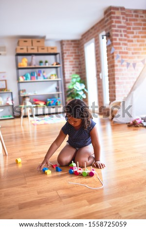 Beautiful toddler girl sitting on the floor playing with train at kindergarten #1558725059