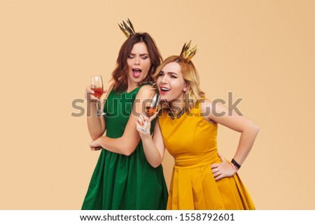 Cheerful playful young women in cocktail dresses and decorative golden crowns having fun together with glasses of champagne on beige background #1558792601