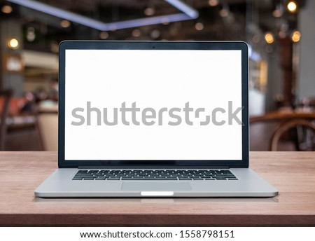 Empty space on wooden Desk with Laptop with blank white screen at coffee shop
